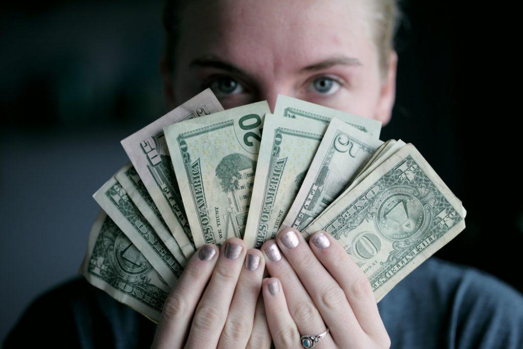 mujer-sosteniendo-dolares-dinero-facil