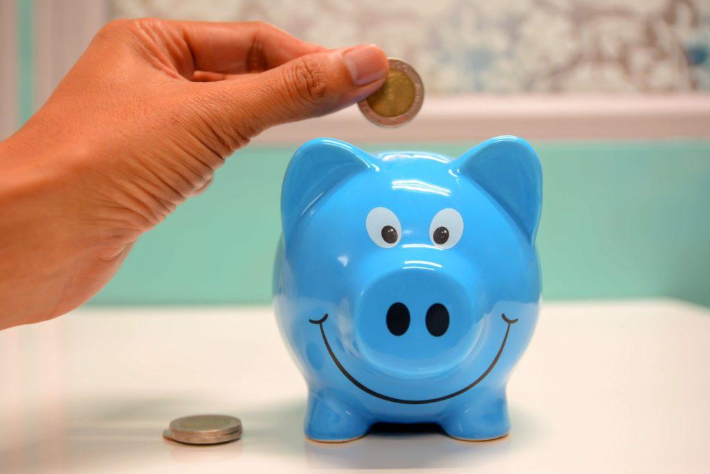 hombre-metiendo-moneda-en-alcancia-de-cerdo-azul
