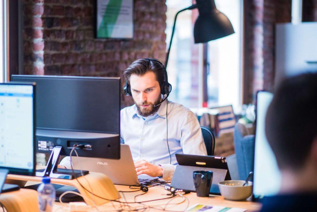 hombre-sentado-frente-a-monitor-con-audifonos