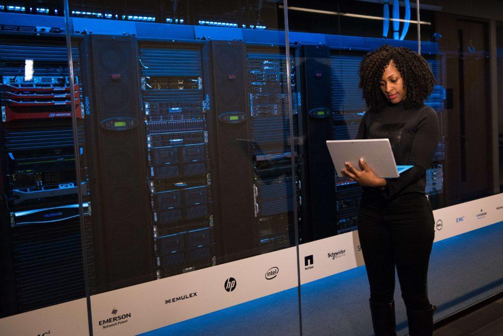 mujer-usando-laptop-frente-servidores